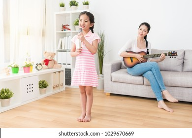 Housewife and young little daughter perform in the living room celebrate for father's day. Mom plays wooden guitar on the sofa and daughter singing in front of the sofa holding a metal microphone.