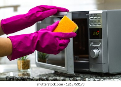 Housewife's hand in rubber gloves cleans the microwave using a sponge
