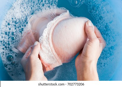 Housewife's hands washing light pink women's bra in the blue basin. Dry cleaning concept. Clothes care. Chores of maid. Regular washing.