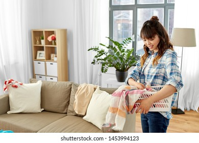 housework, cleaning and housekeeping concept - asian woman with basket picking dirty laundry at home