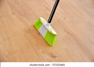 housework, cleaning and housekeeping concept - close up of  broom sweeping floor at home