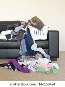 Housework concept of a large pile of laundry dumped on the couch, waiting to be folded and put away