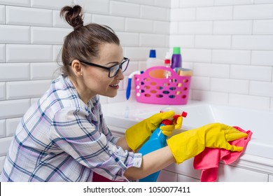 Housework and domestic lifestyle. Woman cleaning bathtub with a cloth