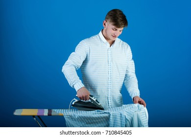 Housework and fashion concept. Guy using iron. Man ironing clothes. Ironing board on blue background.