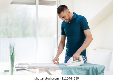 housework and household concept - man ironing shirt on iron board at home - Shutterstock ID 1113444539
