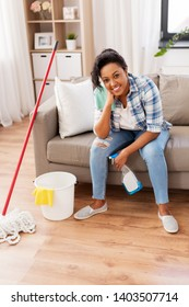 housework and housekeeping concept - african american woman or housewife with dergent, rag, bucket and mop resting after cleaning at home