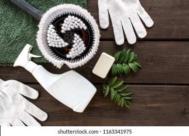 housework, housekeeping and household concept - cleaning stuff on wood background. Flatlay composition of cleaning items, a rag, an atomizer, a laundry soap and a cleaning brush. Top wiev