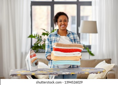 housework, laundry and housekeeping concept - happy african american woman with ironed linen and iron board at home