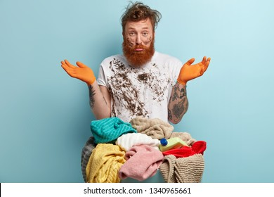 Housework and washing concept. Unshaven red haired man has dirty t shirt, stands near basin full of pile clothes, wears gloves, does laundry, models over blue background, prepares clothes for cleaning