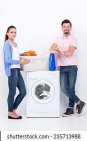 Housework. Young woman and man are doing laundry and looking at the camera.
