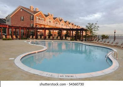 Housing complex with a swimming pool in the foreground photographed in the setting sun