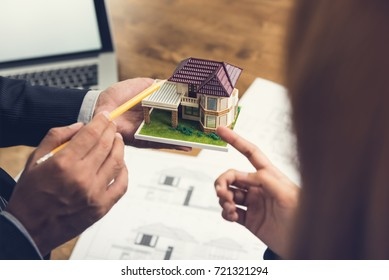 Housing developer agent holding an architectural model and explaining concept to client or architect for real estate development