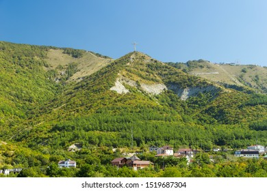 Housing estate at the foot of the Caucasus Mountains. Green hills covered with trees, residential buildings, worship cross on top of hill.