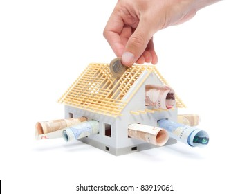 Housing finance, building savings and realty financing (investments) concept. Money and model of the family house.