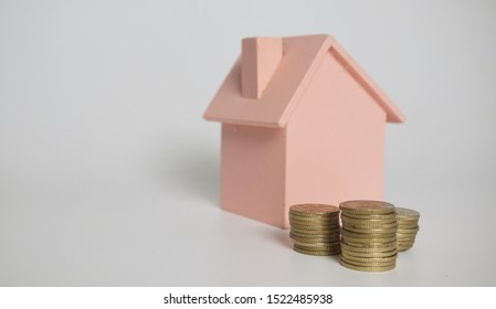 Housing loan concept - dummy wooden house and stack of coins