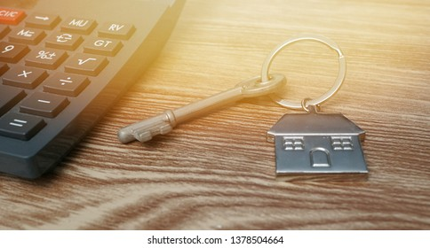 Housing loans and mortgage concept. House key chain and calculator