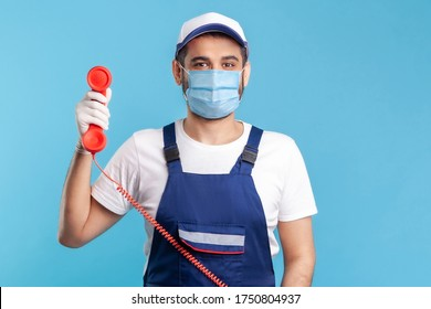 Housing maintenance call centre. Friendly handyman in overalls, mask, safety gloves, holding retro phone handset, answering customer call. Plumber and repair services. indoor studio shot, isolated