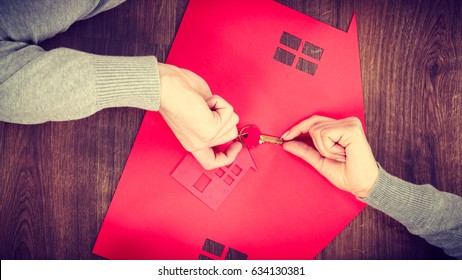 Housing security safety mortgage finances saving concept. People exchanging house keys. Two humans on floor next to home symbol pass keyring.