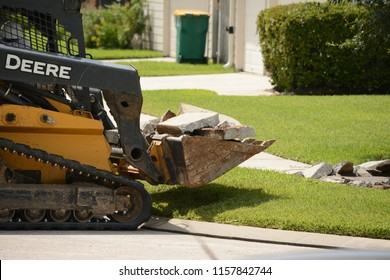 Houston, Texas - August 14, 2018: John Deere Track Loader with front end loader scooping up broken concrete from sidewalk construction.