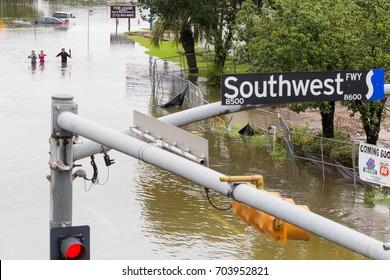 Houston, Texas - August 27, 2017: Houston residents walk across the flooded street in Houston, Texas, USA. Heavy rains from hurricane Harvey caused many flooded areas in Houston.