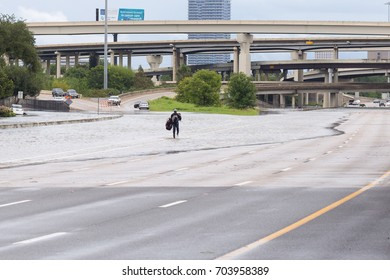 Houston, Texas - August 27, 2017: A stranded motorist carries a child and car seat walks along closed highway 69 in Houston. Hurricane Harvey caused many flooded areas and closed highways in Texas.