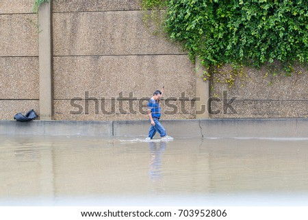 Houston, Texas - August 27, 2017: Houston resident walk across the flooded street in Houston, Texas, USA. Heavy rains from hurricane Harvey caused many flooded areas in Houston.