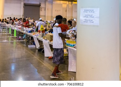 Houston, Texas, August 30, 2017: Another shelter opens at NRG Center as refugees seek safety in Houston. A flood evacuee holding a small child receives necessary supplies