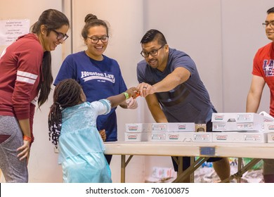 Houston, Texas, August 30, 2017: Another shelter opens at NRG Center as refugees seek safety in Houston. Support workers and volunteers play with a young girl at a shelter
