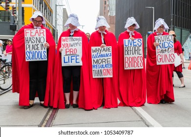 Houston, Texas- March 24, 2018: Activists inspired by The Handmaid's Tale cloaked in stark red robes and white bonnets silently protest against gun violence in schools at the March for Our Lives rally