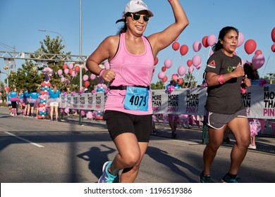 Houston, Texas - October 6, 2018:  Susan G. Komen Race for the Cure - two women running to the finish line as  volunteers cheering on at the end of the race to raise money for cancer research