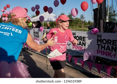 Houston, Texas - October 6, 2018:  Susan G. Komen Race for the Cure - Cancer survivor running to the finish line as  volunteers cheering on at the end of the race to raise money for cancer research