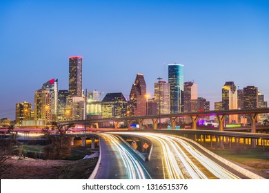 Houston, Texas, USA downtown city skyline and highway at dusk.