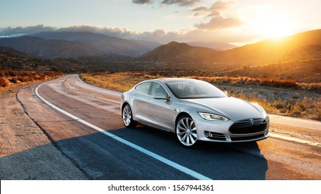 Houston, Texas / USA - November 22nd 2019 : Photograph of a grey Tesla model S driving on the road with the sun setting in the background.