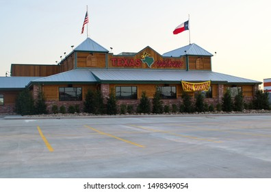 Houston, Texas/USA 09/06/2019: Texas Roadhouse steak house restaurant being prepared for a new opening in Humble, TX with a hiring sign out front. Parking lot in the foreground with flags on the roof.