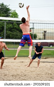 HOUSTON, TX- JUNE 28, 2015: Man SPIKING VOLLEYBALL DURING A SAND VOLLEYBALL TOURNAMENT