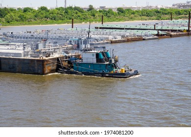 Houston, TX, USA 07.04.2021: Tug Caroline Guidry mowing barges in Houston ship channel. Push tug Caroline Guidry with oil barge. Inland barge storage area.