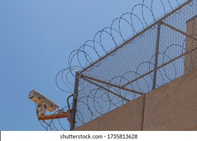 Houston TX/USA - May 2020: High fencing and concertina wire rim the perimeter of Harris County's Baker Street Jail in downtown Houston.