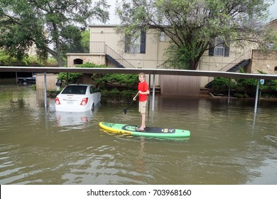 HOUSTON, USA - AUGUST 27, 2017: A teenager rides a  Paddle Board in the flooded streets of houston