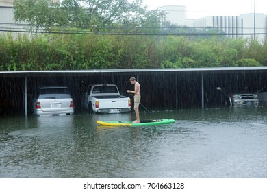 HOUSTON, USA - AUGUST 27, 2017: A teenager rides a  Paddle Board past car parking of Houston. Hurricane Harvey