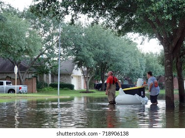 HOUSTON, USA - SEPTEMBER 2, 2017:  People on an inflatable swan carry things from a flooded house