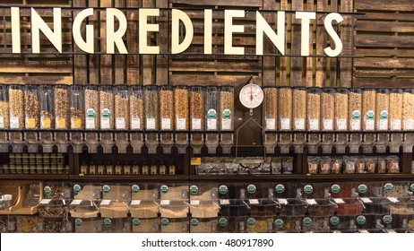 HOUSTON, US-AUG 28, 2016:Row of bins of organic ingredients for bulk sale at Whole Foods Market store at Houston, Texas, US. Fresh nuts and seeds, dried fruits. This chain is a leader in organic foods