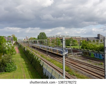 Houten, Utrecht / Netherlands - 05 03 2019: City scape and railway track from trainstation Houten - Castellum to Houten with a Dutch train. White clouds on a sunny day.