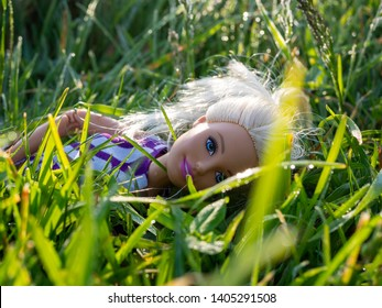 Houten, Utrecht / Netherlands - 23 05 2019: Barbie doll with blond hair in the grass sleeping. Dew on the grass. Close up of Barbie made to move.