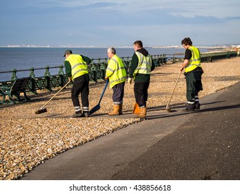 HOVE, ENGLAND - FEBRUARY 24, 2016: A team of council workers begin clearing the shingle thrown up onto the promenade by recent stormy weather.