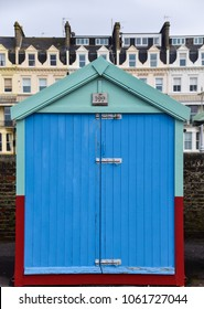 Hove, United Kingdom - March 29 2018:   A bright blue beach hut in front of houses on Kingsway, Hove Seafront