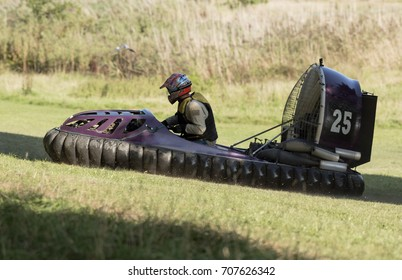 Hovercraft and driver climbing across the grass on a hill during a race in the UK
