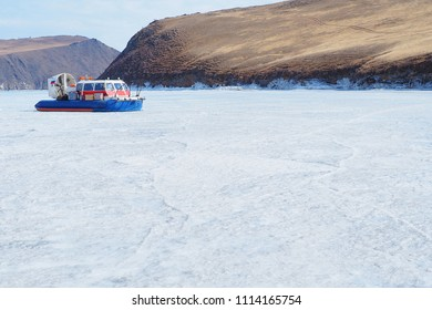Hovercraft running on white ice Baikal lake in late winter beside big brown mountain