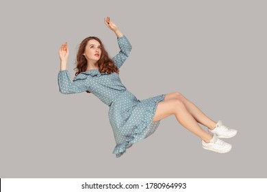 Hovering in air. Full length beautiful pensive girl in vintage ruffle dress levitating flying in mid-air, looking up with dreamy relaxed expression. indoor studio shot isolated on gray background