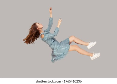 Hovering in air. Relaxed beautiful girl ruffle dress and curly soaring hair levitating, flying in dream with hands up, reaching for something high. indoor studio shot isolated on gray background