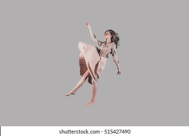 Hovering in the air. Studio shot of attractive young woman hovering in air